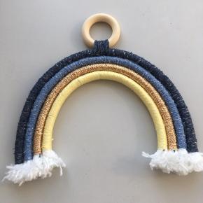 Regnbue - egen produktion. Mål: bredde 17 cm, højde 13 cm (uden træring) 17 cm (med træring). Fin til børneværelse eller i barnevogn.  Farverne: gul, guld, blå og mørkeblå. De blå farver har spil i sig (se billederne).