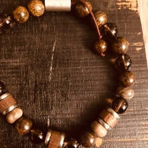 Brunt sten ( tigerøje og røgkvarts)/træ armbånd med træk snore, så længden kan justeres. Alm. Længde  21 cm.  Se foto