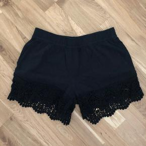 Korte sorte shorts med blondedetalje.
