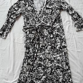 Varetype: Wrap kjole Farve: Sort hvid  Er blevet lagt op af syerske, så den går til lidt under knæene, og buer lidt ind mod midten.  97% viskose, 3% elastan  God stand!