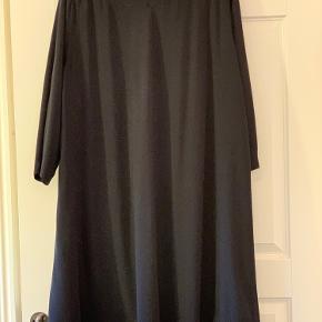Fin sort kjole i A facon med knapeffekt .  Viskose . Brystvidden er 63 x 2 Længden er 101 cm