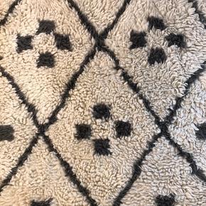 """Rigtig fint gulvtæppe fra Ellos i uld. Modellen er """"Philadelphia"""" uden frynser i hver side. Tæppet er råhvidt med mørkegråt mønster. De grå ser lidt mørkere ud på billedet, end det er i virkeligheden.   B: 140 og l: 200.   Tæpper fælder lidt. Har ingen pletter, men kunne godt trænge til en rens eller en kraftig støvsugning. Sælges derfor billigt."""