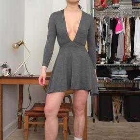 Flot American Apparel kort mørkegrå kjole.  Kjolen er bedst egnet med underdel, da den er kort.   Den er som ny, og fejler ingenting.   Kan afhentes på Vesterbro eller sendes mod betaling af fragt.