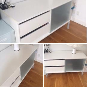BYD!   Tv-bord fra IKEA - Hvidt, 2 skuffer, og 2 glas hylder med glaslåge foran.  Afhentning står køber selv for.   Mål: 114 cm lang, 50 cm bred, 66 cm høj   Har nogle få skrammer på overfalden
