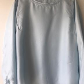 Fineste silke bluse (100 %). Lækker lækker stof, der falder tungt. Fine detaljer i hals og på ærmer. Str 42 - men skrædder har syet siderne ind til str 40. Har desværre blot hængt i skabet.