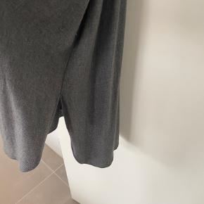 Skjortekjole, lang og lidt længere bagpå. Slidt i begge sider.