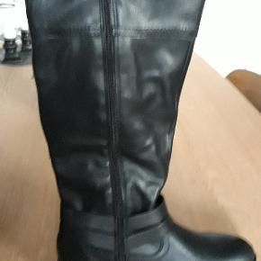 Pæne lange sorte støvler med lynlås. Og dejligt varmt sort foer.  Gode til bredde læg. Lægmål 42 cm. Der er elastik bagpå kanten foroven..  Mærke Tamaris  Str. 40  Aldrig brugt. Da de er for store til mig...