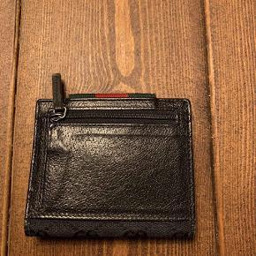 Sælger denne lækre Gucci pung. Den har været brugt en del, men har bare ligget i skabet de sidste 7-8 år. Nu er det på tide at den sælges. Den fremstår pæn, men den mangler dog en lille skrue i spændet foran (kan ses på første billede). Dette har ingen betydning andet end designmæssigt.  Jeg har ikke kvittering eller andet, men jeg står inde for varens ægtehed. Den er købt i Gucci i Berlin.