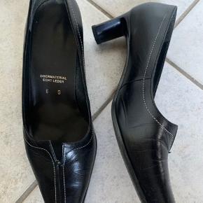 Sort sko med hvide stikninger hælhøjde 4,5 cm.