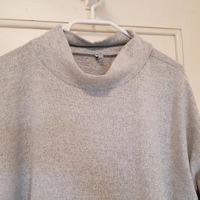 Lækker og superblød lysegrå trøje med høj hals og 3/4 ærmer. Lidt længere bagpå end foran. 95% polyester/5% elestan. Brugt få gange, så er som ny.  Mål Længde: 71cm Bredde: 68cm