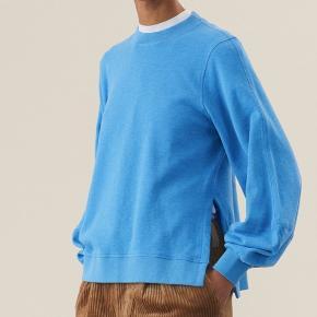 Blå Ganni sweater i 100 % bomuld.  Str. L (til den lidt lille side). Aldrig brugt og sælges da jeg ønsker den i en anden farve. Nypris var 1100