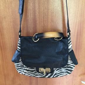 Taske i zebramønster med en anelse guld. Håndtag ligner horn, men er lavet af træ.