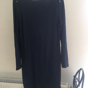 Formsyet kjole med guldknapper på skuldrene.