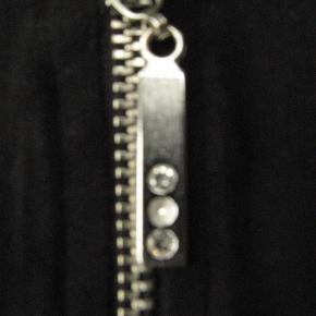 Mærket er Canda. Som det ses, er den ene pyntesten faldet af lynlåsen, derfor den billige pris.  Brystmål ca. 2x64 Længde fra skulderen og ned ca. 69  Materialeangivelsen er klippet ud.  Jeg tager desværre ikke billeder med tøjet på.