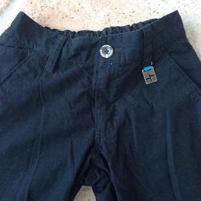 Cross Golfbukser - Junior golfbukser til dreng Størrelse: 146/152 Livvidde: 67 cm i løs tilstand Der er elastik i ryggen af bukserne Hellængde: 75cm