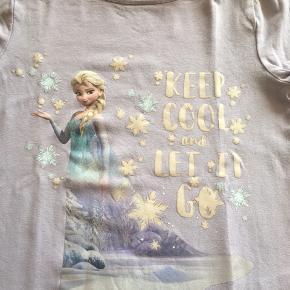 Flot lyselilla bluse med Elsa motiv næsten ikke brugt. Ingen huller/pletter 95% bomuld og 5% elastane.  Ved forsendelse betaler køber fragtomk.