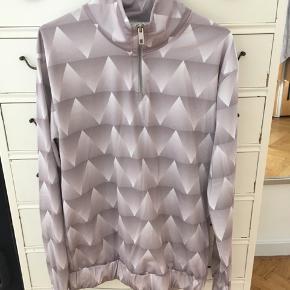 Cool bluse med brede elastikdetaljer nederst og ved ærmerne. Farven er lys metallic lilla, og designet er inspireret af retro cykeltøj.