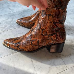 Har været brugt 1-2 gange, og fremstår derfor i rigtig fin stand. Den ene hæl har er lille mærke, se billede tre. Ellers fejler de ikke noget. Materiale er 100 % læder.