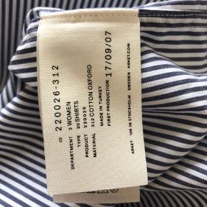 Stribet skjorte fra Arket, slim-fit med ekstra lange ærmer og slidser i siderne af skjorten.  Skjorten er næsten som ny.  Striberne er mørkeblå/grå.