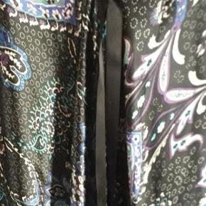 Flot kjole i 97 % polyester og 3% elastan.  Er ikke skåret lige over forneden, og med bindebånd om livet. Lækre farver Størrelsen er M / L