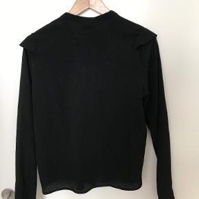 Sort skjorte med flæser. Kan knappes helt op i halsen eller lade stå åben.
