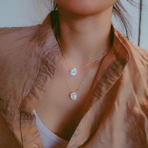 Messing belagt med 18k guld Perlerne er helt naturlige og derfor kan de variere i form og størrelse. Perlerne farve: hvide  Smykkeæske medfølger Prisen er fast og bytte ikke   Skal de sendes:  + 10 DKK med Postnord eller + 33DKK med DAO via Trendsales