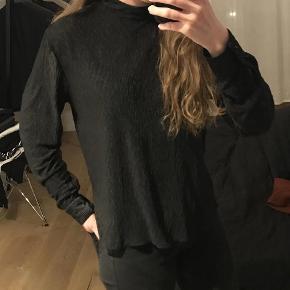 Varetype: Bluse Farve: Sort  Helt ny Hosbjerg bluse med høj hals og knapper i nakken samt i ærmerne. Str. S, men passer normalt str. 38. Den er fremstillet i lækkert blødt stof med rynker i, så den er super flot og kræver ikke at den stryges.