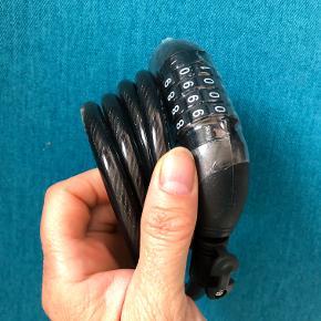 Cykellås med kode. Sort spirallås.  Til cykel, knallert, barnevogn, rollator løbehjul....og....  Ca. 150 cm lang. Metalwire beklædt med plastikslange.  Har aldrig været brugt; men brugsanvisningen mangler. Den kan googles, så du selv kan stille en personlig kode.  Nypris 100 kr.  Sælges nu for kun 40 kr. + evt. porto.  Kan afhentes på Frederiksberg.