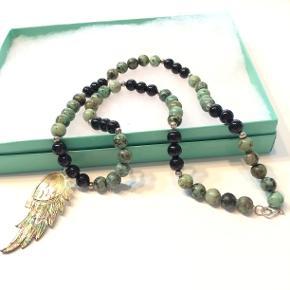 Virkelig smuk halskæde udarbejdet i grønne kambala sten og sort onyx, sølvperler og sølvlås, samt en perlemor vinge som vedhæng.  Kæden er 57 cm lang.  Jeg sender gerne med DAO pakkepost, hvis du ikke kigger forbi og henter den  Mvh Lise