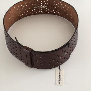 Flot læderbælte i mørkebrun med hulmønster. 8 cm bredt på det bredeste sted og 104 cm lang. Aldrig brugt og med prisskilt 🌸