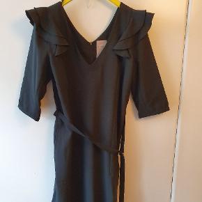 Vidunderlig, smart og anvendelig kjole i uldmix, str. L fra Benedikte Utzon. Kjolen har V-udskæring både for og bag, kort lynlås i nakken, stiklommer i siden, 3/4 ærmer med lynlåsdetalje og bindebånd med metalring. Kjolen har en markant wau-effekt med de smukkeste skulderdetaljer ( se fotos). Måler over brystet 104 cm, og længden er 98 cm. Kjolen kan let styles til fest, kontoret eller hverdag. Ny - og meget smuk. Kulsort - trods lyset på billederne! BYTTER IKKE!