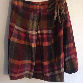 Multifarvet nederdel i marine uld. Str 38. Den er normal str. 38 men er justerbar ifht. Livvidden. Den kan gå op til 78 cm livvidden. Ellers kan den gå ned i lilviden med en knap og de to bindebånd i siden. Længden er 57 cm