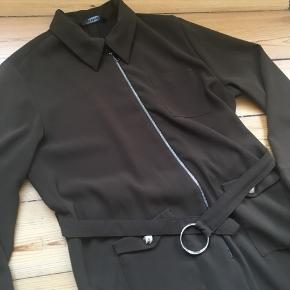 Armygrøn buksedragt fra Zara. Buksedragten har en lynlås ved maven, lommer samt bredde bukseben. Derudover er der et elastisk bælte i hoften, som fremhæver taljen.