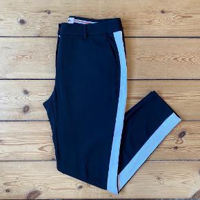 """Sorte bukser med bred, hvid stribe langs siderne på benene fra Custommade  Har været brugt en enkelt gang, og siden da har de blot hængt i skabet  Modellen hedder """"Muno w. Galon"""""""