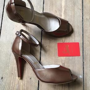 Skoene er aldrig blevet brugt, har bare stået i skabet. Der står str. 40 på skoene, men jeg er normalt en 38-39 og passer dem perfekt.
