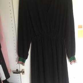 Sød kjole med flot glimmerdetalje ved håndledet. Strammer ind i taljen og har en lille-dyb v-udskæring. Sælges kun da jeg ikke får denne brugt.