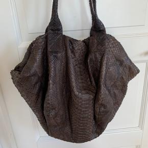 Brun taske i slangeskind fra Rabens Saloner. Den er i super fin stand. Kun brugt meget lidt. Lukkes med lynlås. Har et rum indvendig med lynlås samt to mindre åbne rum. Mål: Bredde ca 52 cm, højde ca 41 cm. Længde på lynlås: 32 cm.