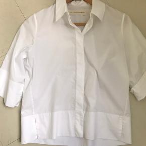 Jan Machenhauer. Fin hvid kort skjorte i crispy cotton. Lige i snittet.  Fine detaljer, skjult knaplukning, slids i bunden.  Længde 56 cm Bredde 48 cm (x2)