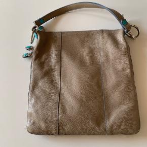 Lækker lædertaske fra Gabs i beige med turkise mærkninger og indtræk. Kan laves til rygsæk, lang og kort strop samt udvides.