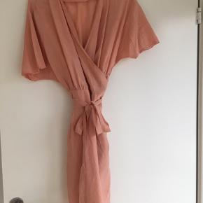 Smuk slå om kjole fra Ganni i ferskenfarve.
