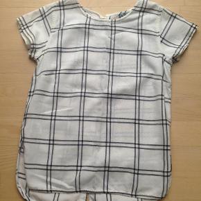 Varetype: Skjorte Størrelse: 158/164 12-14 år Farve: Sort/hvid  Har en lille misfarvning ved halsudskæringen -se billede.