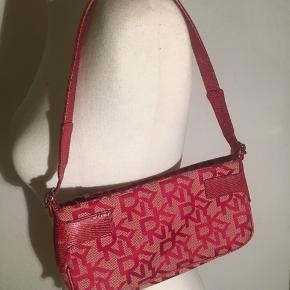 Lille håndtaske fra dkny med all over logo print - en blanding mellem pink og rød i farven. Helt som ny.