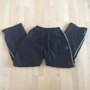 Hummel bukser i sort med grå stribe langs benet. Ekstra vidde/lynlås forneden i benet. Lommer i siden. Åndbare bukser med svedtransporterende stof. Brugt få gange. Nypris 700 kr.  Benvidde: 24 cm Benlængde: 72 cm Livvidde: svær at måle grundet elastik men kan strækkes op til 98 cm