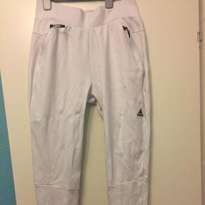 Hvide Adidas træningsbukser str. M. De har ridebukse facon og er smalle forneden men brede i lårene. Lynlås nederst bagpå. Lommer foran. De er i den gode ende af god men brugt.