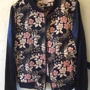 Flot bomber jakke med det smukkeste blomstermønster  Lynlås  Fnuller ved ærmeslutning  Bytter ikke