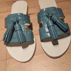 Sandaler med kvaster i flot blå farve. Ikke rigtig brugt, men har lidt mærker foran.  Kan afhentes i Roskilde, tages med til Odense eller sendes.