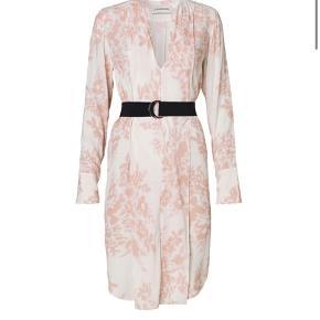 Elegant kjole med dekorativt blomsterprint, der fremhæver de feminine former. Med flatterende læg, dyb V-udskæring og sort bælte, der skaber kontrast, og definerer taljen. - Aftageligt bælte - med knapper på ærmerne - rundet kantning - 100 % viskose - Tør rensning  Lidt stor i størrelsen, så den kan også passes af en S og måske lille M.
