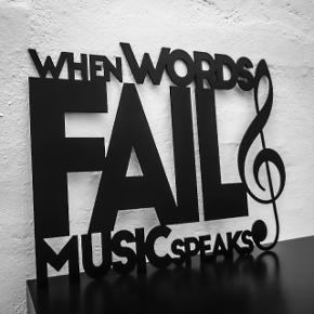 """Dekorativt skilt udskåret i 2 mm stål og sortlakeret. Tekst: """"When words fail music speaks"""".  Skiltet kan ophænges i selve udskæring med 2 sorte søm, som medfølger. Ellers kan skiltet stilles op ad væg, hylde ell. lignende.  Bredde × højde: 41x32 cm. 139 kr. 62x48,5 cm. 249 kr.  Fragt pris: 29 kr u/omdeling ell. omdeling til erhvervsadresse. 48 kr m/omdeling til privat adresse."""