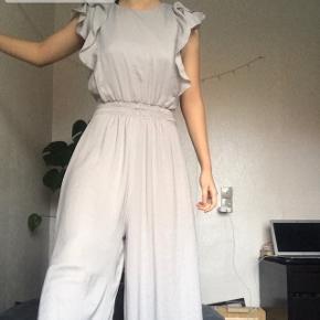 Beige / grå buksedragt fra zara. Gulv lang og meget elegant, lukkes bagfra. Har elastik ved taljen, som kan ses på billede nr. 2  Kan sendes med DAO