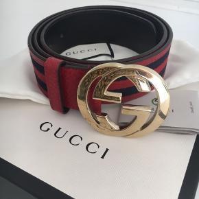 Gucci bælte i rød og marine.  Str. 85 cm ( kan dog laves ekstra huller).   Brugt sparsomt, lidt slid på spændet. Resten af bæltet fremstå som nyt. Kasse og dustbag medfølger.